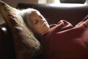 portrait of mature woman sleeping with blanket over her